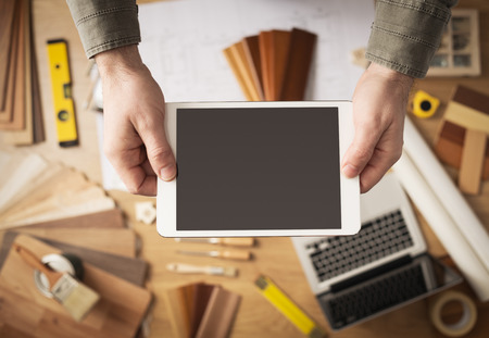 it tech: Home renovation and technology concept, male hands holding a digital tablet with work table and tools Stock Photo