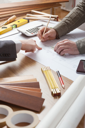 quantity: Businessman and construction engineer working together, the customer is pointing on the project on the desk Stock Photo