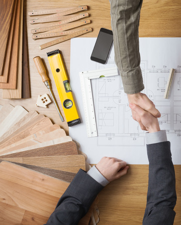 Customer businessman and construction engineer working together on a building project, they are shaking hands, desktop with draft and tools
