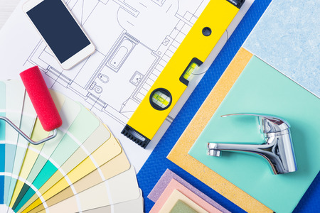 swatches: Home repair and decorating concept with color swatches, tiles, faucets and mobile phone, top view