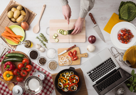 Man cooking in the kitchen and slicing vegetables on a chopping board, top view