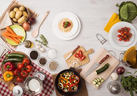 Pasta met tomatensaus en basilicum op aanrecht, groenten en gebruiksvoorwerpen rondom, bovenaanzicht Stockfoto