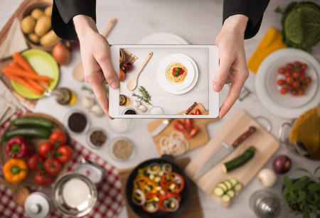 Cook\'s hands holding a touch screen tablet close up, kitchen table with food ingredients, vegetables and utensils