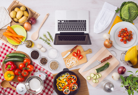 ingredient: Home kitchen table top view with laptop, food ingredients, raw vegetables, kitchenware and utensils, top view