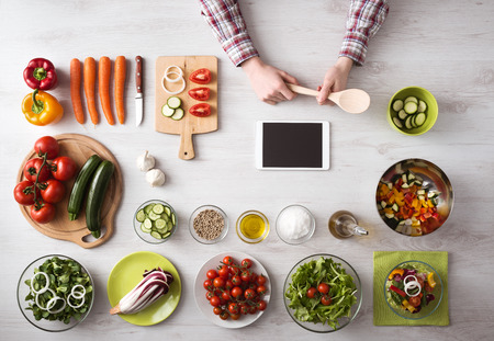 �cooking: La mano del hombre cocinar en casa con la tableta de pantalla t�ctil, verduras frescas y utensilios de cocina por todas partes, vista desde arriba Foto de archivo