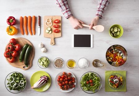 Man hand koken thuis met touch screen tablet, verse groenten en keukengerei rondom, bovenaanzicht