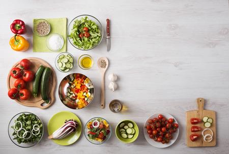 comida: Conceito saudável comer com legumes frescos e saladeiras na cozinha bancada de madeira, cópia espaço à direita, vista de cima
