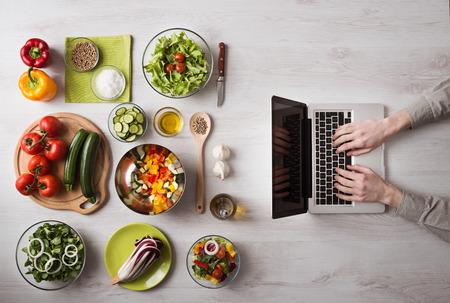 nutrición: Hombre en la cocina en busca de recetas en su computadora portátil con ingredientes de alimentos y verduras frescas a la izquierda, vista desde arriba