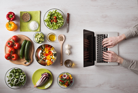 food dish: Man in the kitchen searching for recipes on his laptop with food ingredients and fresh vegetables on the left, top view