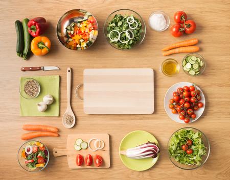 salad plate: Cocina vegetariana creativa en concepto de hogar con verduras frescas picadas saludables, ensaladas y utensilios de cocina de madera, vista desde arriba, con copia espacio
