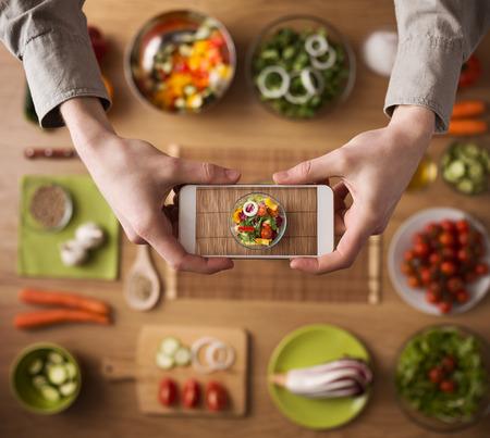 nutrición: Hombre que sostiene un teléfono inteligente manos cerca, mesa de la cocina encimera Foto de archivo