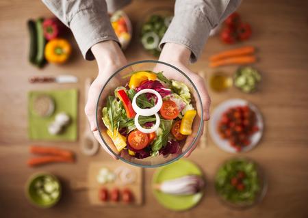 nutricion: Manos que sostienen una ensalada vegetariana fresca saludable en un cuenco, verduras crudas frescas