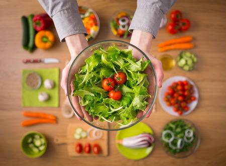 ensalada de tomate: Manos que sostienen una ensalada vegetariana fresca saludable en un cuenco, verduras crudas frescas