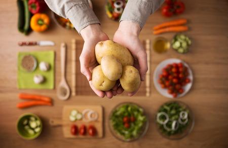 Handen die vers geoogste aardappelen met rauwe kleurrijke groenten van het seizoen