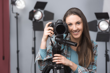 lighting equipment: Young female photographer posing in her studio with a digital camera on a tripod and lighting equipment  Stock Photo