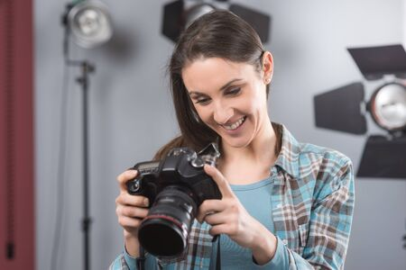 lighting equipment: Young female photographer posing in her professional studio, holding a digital camera with lighting equipment on