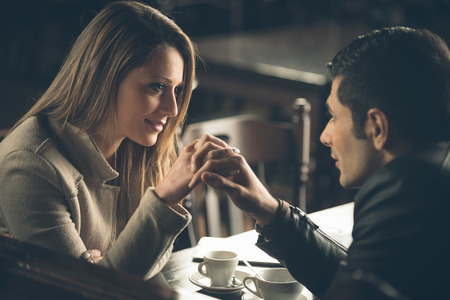Romantic couple dating at the bar with hands clasped Foto de archivo
