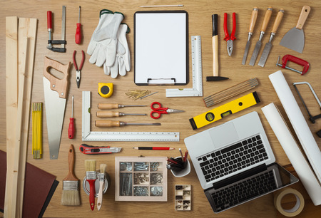 Blank project on a clipboard with DIY tools all around on a work table, top view Stock Photo