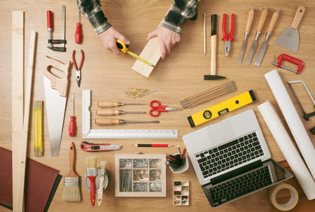Male hands measuring a wooden plank with a tape measure with DIY work tools all around on a work table, top view Stock Photo