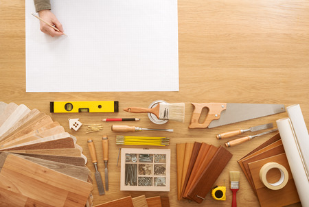 workbench: Man sketching a DIY project on a work table with construction tools top view, hobby and crafts concept