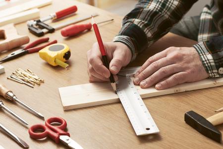 řemeslo: Člověk, který pracoval na projektu, DIY a měření dřevěné prkno s pracovními nástroji všude kolem, ruce zblízka