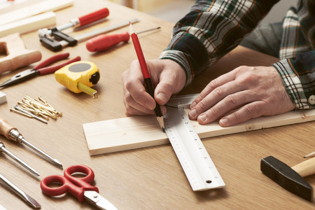 Man working on a DIY project and measuring a wooden plank with work tools all around, hands close up Stockfoto