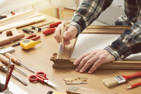 brocha de pintura: Hombre barnizado un marco de madera manos cerca con herramientas de bricolaje en una mesa de trabajo
