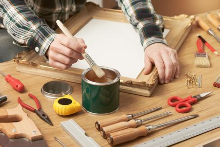 carpintero: Decorador barnizar un marco de madera manos cerca con herramientas de bricolaje, afición y el concepto de artesanía
