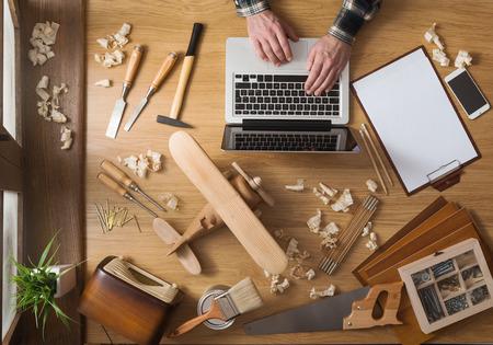Uomo che lavora ad un progetto fai da te con il suo portatile, trucioli di legno e strumenti di carpenteria tutto intorno, vista dall'alto