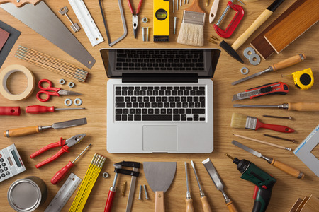 wood craft: Laptop on a work table with DIY and construction tools all around, top view, hobby and crafts concept Stock Photo