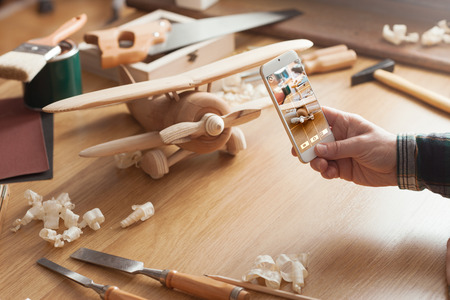 Man fotografeert zijn handgemaakt houten speelgoed vliegtuig met een slimme telefoon op een werktafel