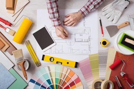 pintor de casas: Decorador profesional sobre la base de un proyecto de la casa con las herramientas de trabajo, rodillos de pintura y muestras de color por todas partes, vista desde arriba