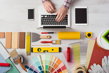 Professional decorator's hands working at his desk and typing on a laptop, color swatches, paint rollers and tools on work table, top view