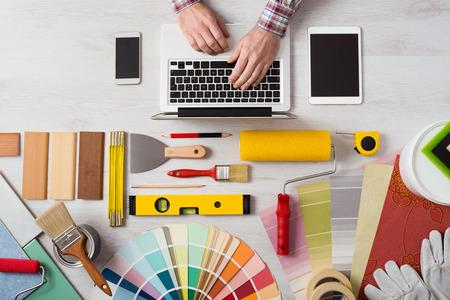 pintor: Manos del decorador profesional que trabaja en su escritorio y escribiendo en un ordenador portátil, muestras de color, los rodillos de pintura y herramientas sobre la mesa de trabajo, vista desde arriba