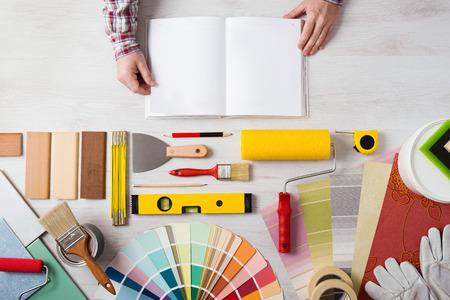 pintor: Tomados de la mano del manual abierto de formación de bricolaje con herramientas de trabajo, muestras de color y rodillos de pintura en el fondo, vista desde arriba