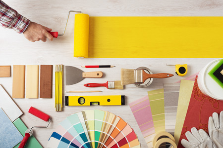 Decorator holding a painting roller and painting a wooden surface, work tools and swatches at bottom, banner with copy space Stok Fotoğraf