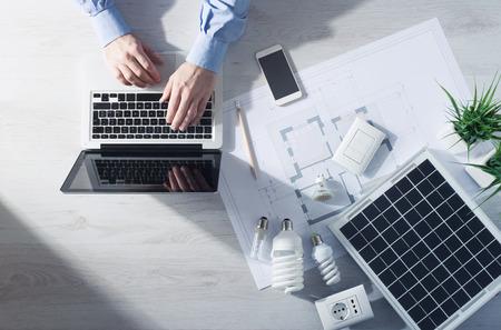 Man werken aan zijn bureau op een laptop met energiezuinige spaarlampen, een zonnepaneel en een huis-project, bovenaanzicht