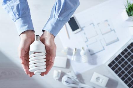 ahorro energia: Hombre que sostiene un proyecto de energ�a CFL l�mpara de ahorro, el panel solar y la casa, vista desde arriba Foto de archivo