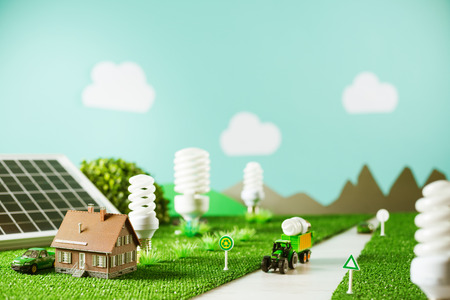 eco house: Environmental friendly toy town with model house, CFL lamps as trees and tractor carrying a light bulb Stock Photo
