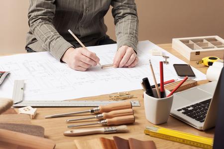 建築家と建築士のオフィスの机で働く手クローズ アップ、彼は鉛筆と、定規建物ドラフト図面