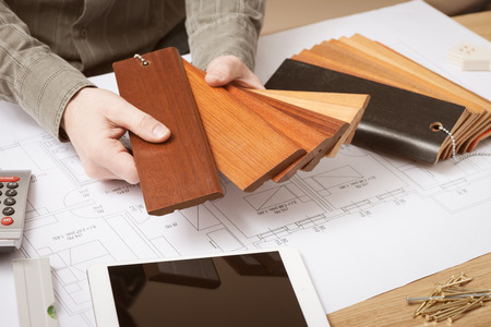 Professional interior designer holding wood swatches for baseboard and skirting, hands close up with desktop