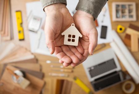 Agente inmobiliario que sostiene una pequeña casa, de escritorio con herramientas, muestras de madera y equipo Foto de archivo