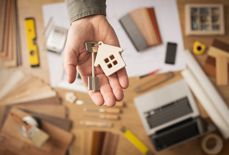 Real estate agent handing over a house key, desktop with tools, wood swatches and computer