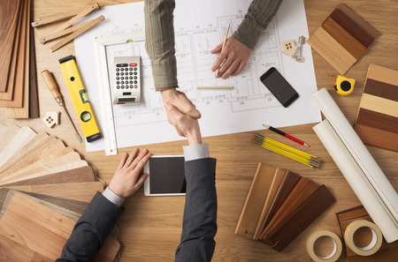Architect and customer businessman shaking hands top view, desktop with building project, tools and wood swatches