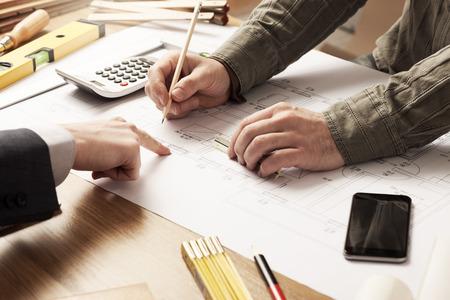 arquitecto: Empresario e ingeniero de construcci�n que trabajan juntos, el cliente est� se�alando en el proyecto sobre el escritorio