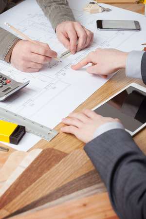 Customer businessman and architect working together, one is pointing on a blueprint on the desk photo