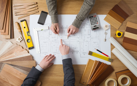Customer businessman and construction engineer working together on a building project, desktop top view Stockfoto