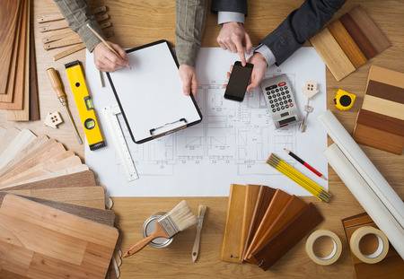carpentry: Business people working together on a building project, desktop top view with tools, wood swatches, mobile phone and blueprint
