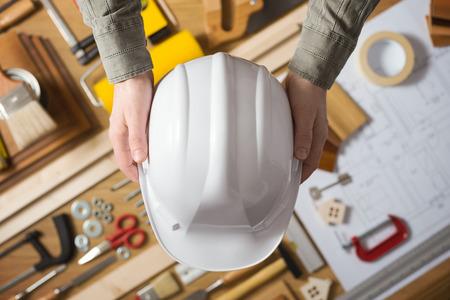 hardware: Manos sosteniendo un casco de seguridad de protecci�n contra una mesa de trabajo con herramientas de hardware y de la construcci�n, vista desde arriba
