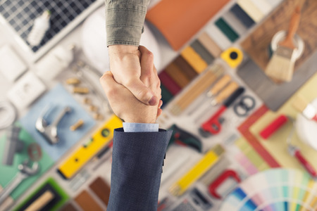 people shaking hands: Businessmen shaking hands, construction and home renovation tools , top view